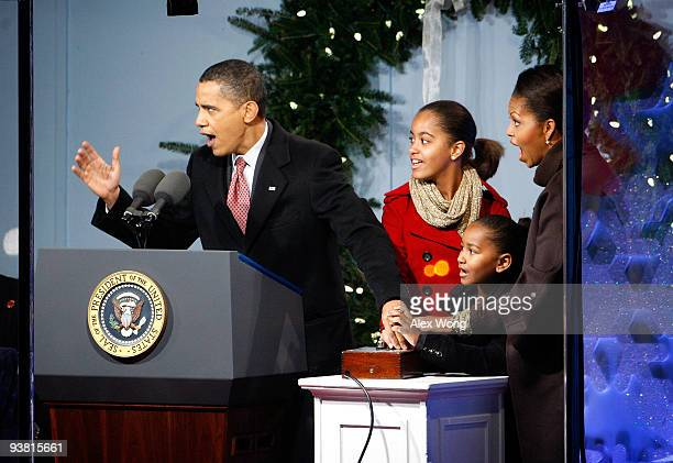 US President Barack Obama presses the button to light up the National Christmas Tree with daughters Malia and Sasha and first lady Michelle during...