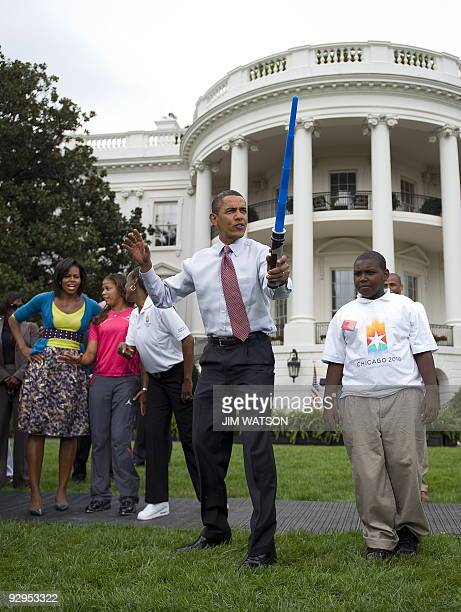 US President Barack Obama pretends to fence with a lightsaber as First Lady Michelle Obama watchs during an event on Olympics Paralympics and youth...