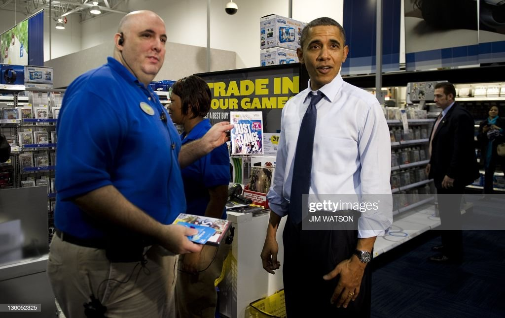 US President <a gi-track='captionPersonalityLinkClicked' href=/galleries/search?phrase=Barack+Obama&family=editorial&specificpeople=203260 ng-click='$event.stopPropagation()'>Barack Obama</a> (R) purchases 'Just Dance 3' for the Wii gaming console while shopping at Best Buy in Alexandria, Virginia, December 21, 2011. AFP PHOTO/Jim WATSON
