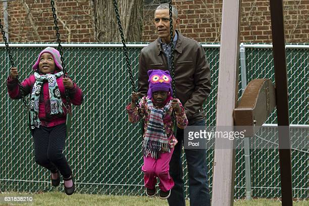 US President Barack Obama pushes children on swings on 'Malia and Sasha's Castle' a playset that was formerly used by the Obama children at the White...
