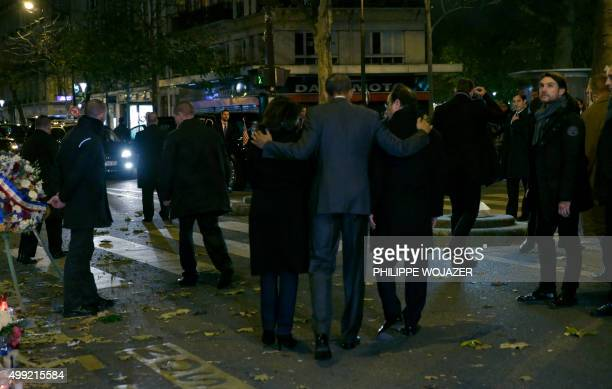 US President Barack Obama puts his arms around French President Francois Hollande and Paris Mayor Anne Hildago after paying their respects at the...