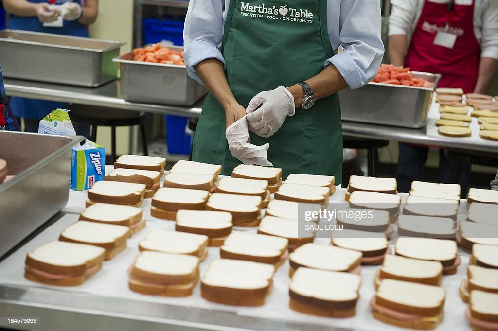 US President Barack Obama puts on protective gloves prior to making bologna sandwiches at Martha's Table in Washington, DC, October 14, 2013, as the crisis over a US government shutdown and debt ceiling standoff continues into the third week of the shutdown. The non-profit organization helps low income and homeless families and many of the current volunteers are furloughed federal workers. AFP PHOTO / Saul LOEB