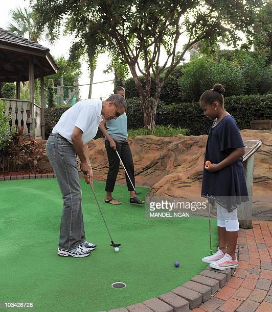 US President Barack Obama putss as First Lady Michelle Obama and daughter Sasha watch on the first hole during a round of mini golf at Pirate's...