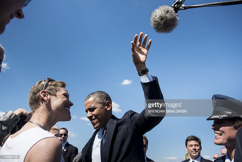 US President Barack Obama reaches for a boom microphone while joking with a baby in a crowd of greeters at Whiteman Air Force Base July 24, 2013 in Missouri. Obama is traveling to Illinois and Missouri to speak about the economy. AFP PHOTO/Brendan SMIALOWSKI
