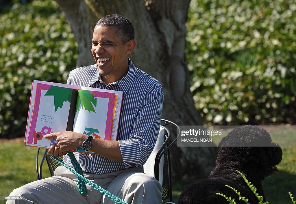 US President Barack Obama reads 'Chicka Chicka Boom Boom' as Bo, the Obama family dog, stand next to him during the annual Easter Egg Roll on April 1, 2013 on the South Lawn of the White House in Washington, DC. AFP PHOTO/Mandel NGAN
