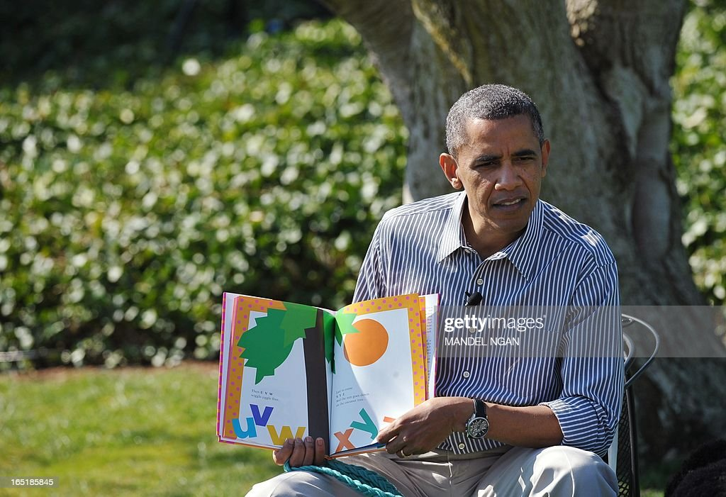 US President Barack Obama reads 'Chicka Chicka Boom Boom' to children during the annual Easter Egg Roll on April 1, 2013 on the South Lawn of the White House in Washington, DC. AFP PHOTO/Mandel NGAN