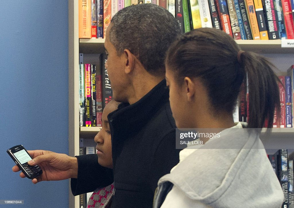 US President Barack Obama reads from his Blackberry cellphone alongside his daughters Sasha (L) and Malia (R) during a shopping trip to One More Page Books on Small Business Saturday, which promotes shopping at local small businesses, in the Falls Church neighborhood of Arlington, Virginia, on November 24, 2012. AFP PHOTO / Saul LOEB