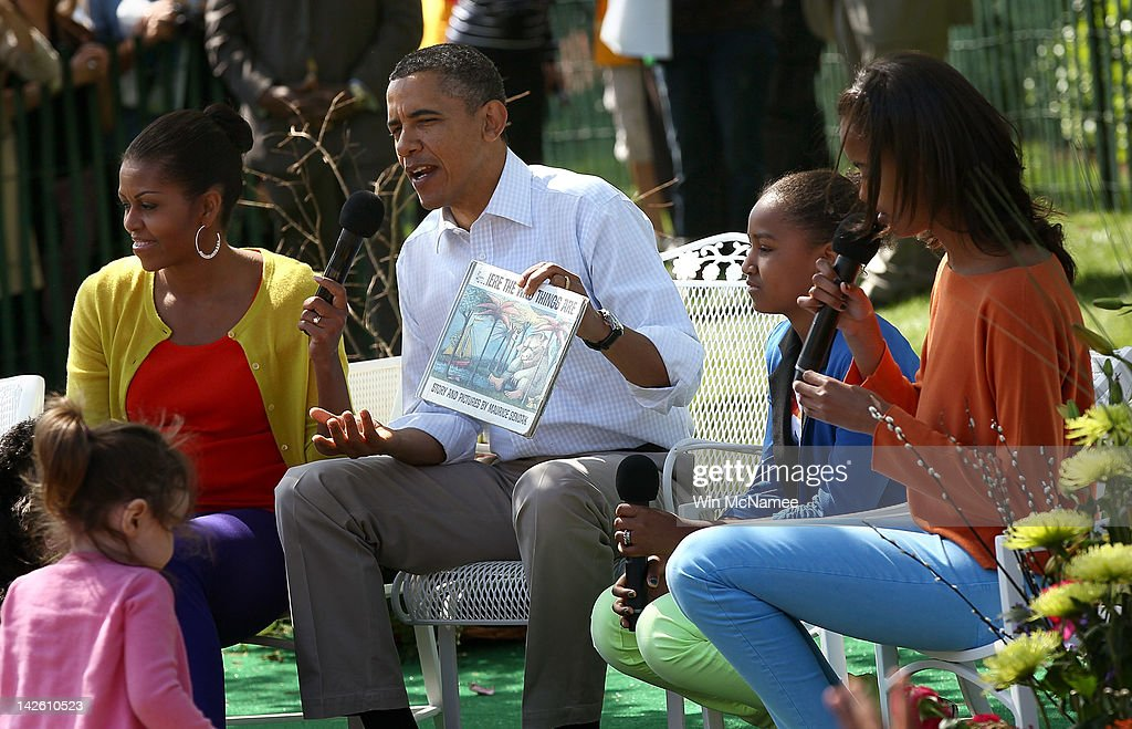U.S. President <a gi-track='captionPersonalityLinkClicked' href=/galleries/search?phrase=Barack+Obama&family=editorial&specificpeople=203260 ng-click='$event.stopPropagation()'>Barack Obama</a> reads from the book 'Where The Wild Things Are' with first lady <a gi-track='captionPersonalityLinkClicked' href=/galleries/search?phrase=Michelle+Obama&family=editorial&specificpeople=2528864 ng-click='$event.stopPropagation()'>Michelle Obama</a> (L) and his daughters Sasha (2nd R) and Malia (R) during the White House Easter Egg Roll on the South Lawn of the White House April 9, 2012 in Washington, DC. Thousands of people people are expected to attend the 134-year-old tradition of rolling colored eggs down the White House lawn that was started by President Rutherford B. Hayes in 1878.