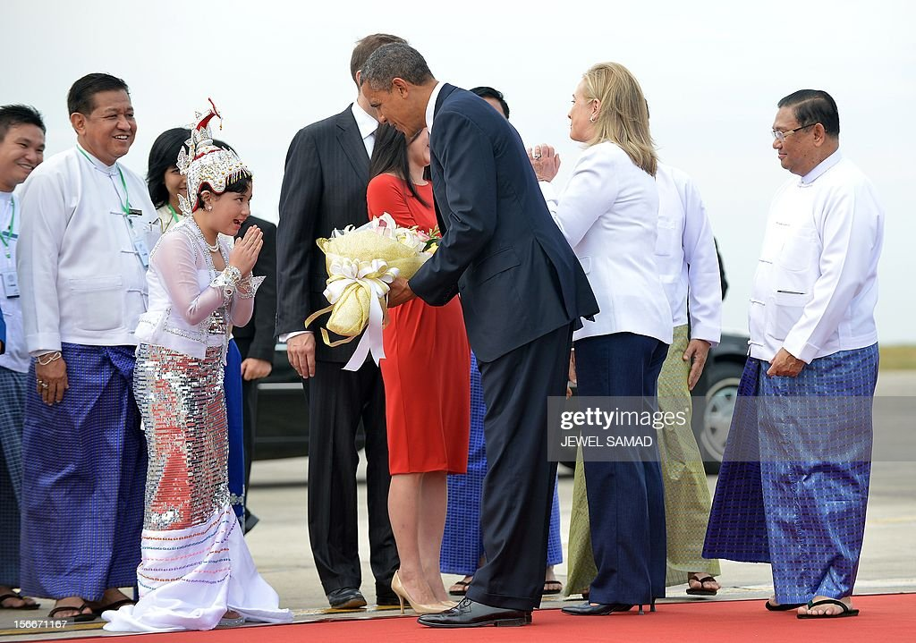 US President Barack Obama (C) receives a bunch of flowers from a girl next to Secretary of State Hillary Clinton (2nd R) on arrival at the Yangon International airport on November 19, 2012. Obama arrived in Myanmar for a historic visit aimed at encouraging a string of dramatic political reforms in the former pariah state.