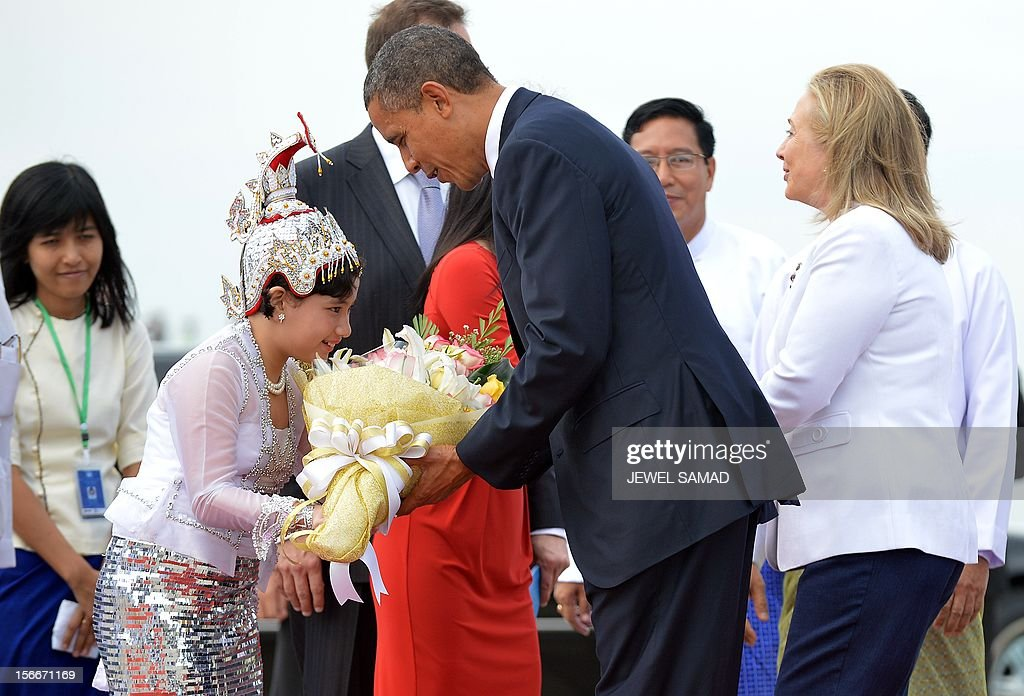 US President Barack Obama (C) receives a bunch of flowers from a girl next to Secretary of State Hillary Clinton (R) on arrival at the Yangon International airport on November 19, 2012. Obama arrived in Myanmar for a historic visit aimed at encouraging a string of dramatic political reforms in the former pariah state.
