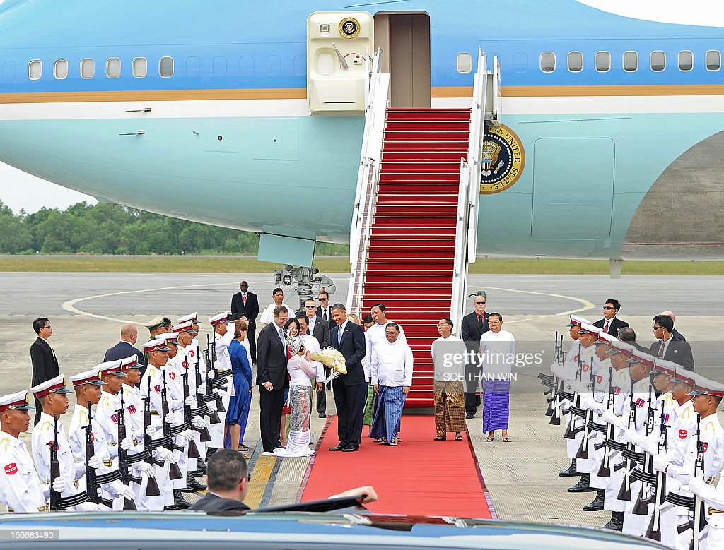 US President Barack Obama (C) receives a bunch of flowers from a girl on arrival at the Yangon International airport on November 19, 2012. Obama arrived in Myanmar for a historic visit aimed at encouraging a string of dramatic political reforms in the former pariah state. AFP PHOTO/ Soe Than WIN