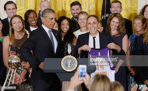 President Barack Obama receives a jersey from Diana Taurasi of the WNBA champion Phoenix Mercury during an event in the East Room at the White House...