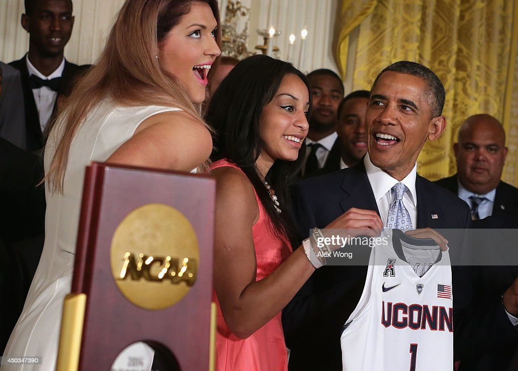 U.S. President <a gi-track='captionPersonalityLinkClicked' href=/galleries/search?phrase=Barack+Obama&family=editorial&specificpeople=203260 ng-click='$event.stopPropagation()'>Barack Obama</a> (R) receives a jersey from point guard <a gi-track='captionPersonalityLinkClicked' href=/galleries/search?phrase=Bria+Hartley&family=editorial&specificpeople=7334401 ng-click='$event.stopPropagation()'>Bria Hartley</a> (2nd L) and center <a gi-track='captionPersonalityLinkClicked' href=/galleries/search?phrase=Stefanie+Dolson&family=editorial&specificpeople=7369130 ng-click='$event.stopPropagation()'>Stefanie Dolson</a> (L) of the University of Connecticut women's basketball team during an East Room event at the White House June 9, 2014 in Washington, DC. President Obama hosted the NCAA Champion UConn Huskies Men's and Women's Basketball teams to honor the teams and their 2014 NCAA Championships.