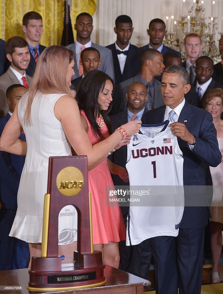 US President Barack Obama (R) receives a jersey from Stefanie Dolson (L) and Bria Hartley (C) of the UConn women's Huskies during an event in honor of the NCAA 2014 Champions, the UConn Huskies Mens and Womens Basketball teams in the East Room of the White House June 9, 2014 in Washington, DC. AFP PHOTO/Mandel NGAN