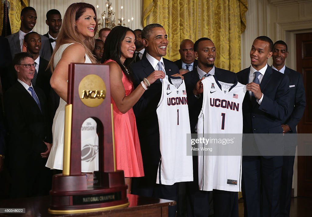U.S. President Barack Obama (3rd L) receives a jerseys from point guard Bria Hartley (2nd L) and center Stefanie Dolson (L) of the University of Connecticut women's basketball team and Ryan Boatright (4th L) and point guard Shabazz Napier (R) of the University of Connecticut men's basketball team during an East Room event at the White House June 9, 2014 in Washington, DC. President Obama hosted the NCAA Champion UConn Huskies Men's and Women's Basketball teams to honor the teams and their 2014 NCAA Championships.