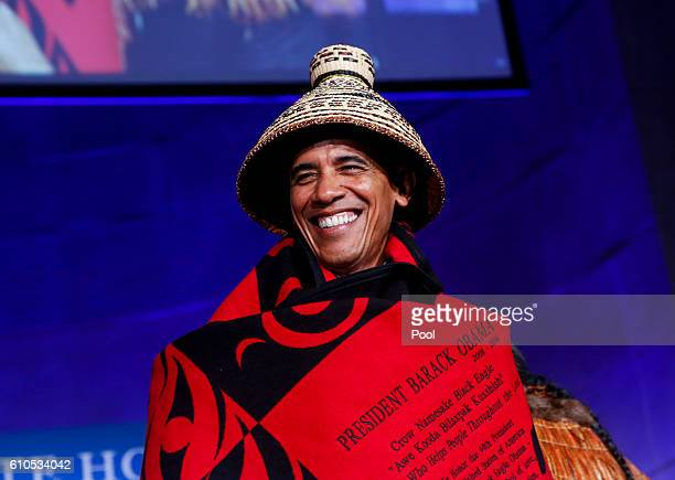 President Barack Obama receives a traditional blanket and hat during the 2016 White House Tribal Nations Conference at the Andrew W Mellon Auditorium...