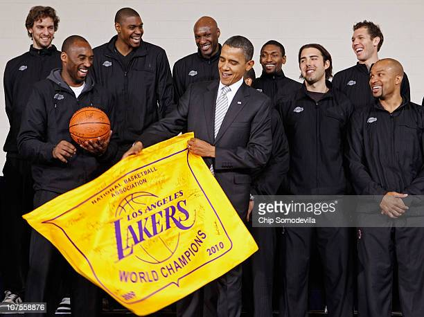 US President Barack Obama receives an autographed championship flag and basketball from members of the Los Angeles Lakers Paul Gasol Kobe Bryant...