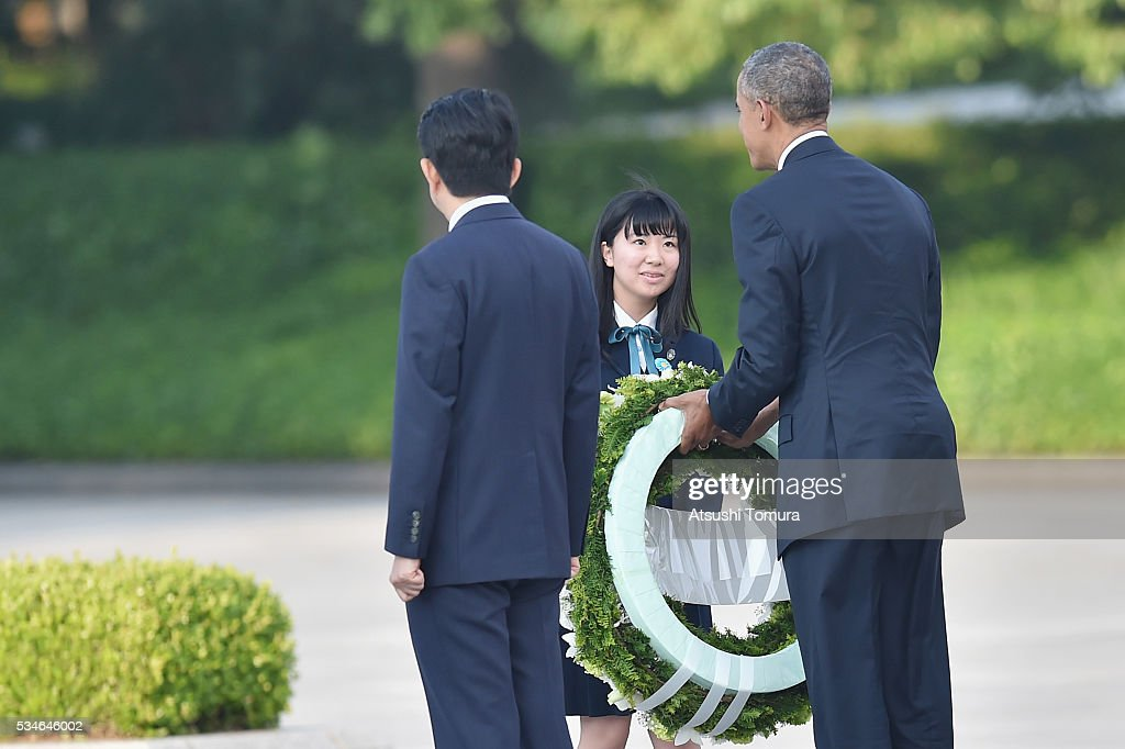 U.S. President <a gi-track='captionPersonalityLinkClicked' href=/galleries/search?phrase=Barack+Obama&family=editorial&specificpeople=203260 ng-click='$event.stopPropagation()'>Barack Obama</a> (R) receives flowers to give as Japanese Prime Minister <a gi-track='captionPersonalityLinkClicked' href=/galleries/search?phrase=Shinzo+Abe&family=editorial&specificpeople=559017 ng-click='$event.stopPropagation()'>Shinzo Abe</a> (L) looks on during U.S. President Obama's visit to the Hiroshima Peace Memorial Park on May 27, 2016 in Hiroshima, Japan. It is the first time U.S. President makes an official visit to Hiroshima, the site where the atomic bomb was dropped in the end of World War II on August 6, 1945.