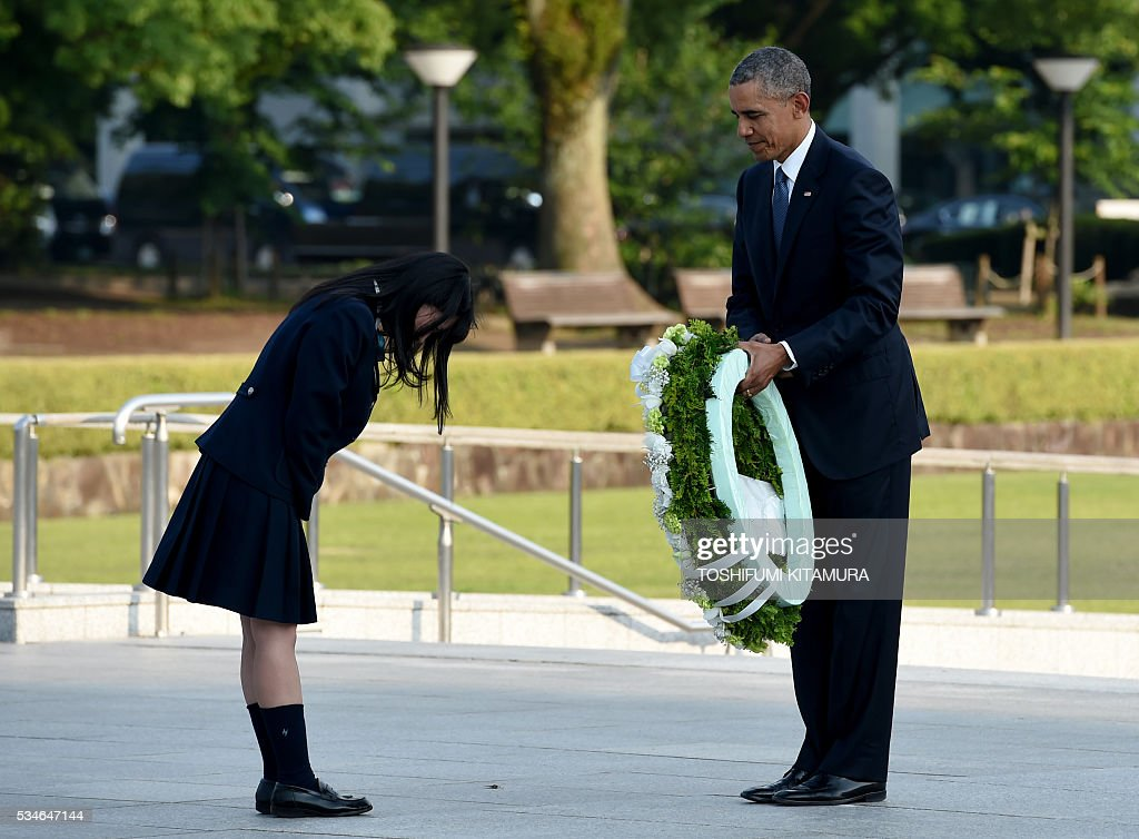 US President Barack Obama (R) recieves a bow from a student (L) at the cenotaph in the Peace Momorial park in Hiroshima on May 27, 2016. Obama became the first sitting US leader to visit the site that ushered in the age of nuclear conflict. / AFP / TOSHIFUMI