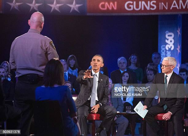 US President Barack Obama replies to a question by Arizona Sheriff Paul Babeu at a town hall meeting with CNN's Anderson Cooper on reducing gun...