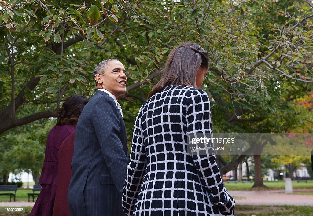 US President Barack Obama responds to a reporter's question while walking with his family from the White House, across Lafayette Park to Saint John's Episcopal Church for Sunday services on October 27, 2013 in Washington, DC. AFP PHOTO/Mandel NGAN