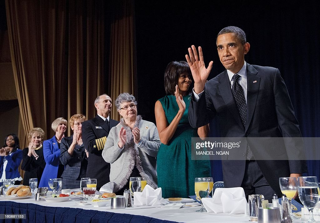 US President Barack Obama returns to his seat after speaking at the National Prayer Breakfast on February 7, 2013 at a hotel in Washington, DC. From left are: Olympic gold medalist Gabrielle Douglas, Elizabeth Dole, Rep. Janice Hahn, D-CA, Darleen Greenert, Chief of Naval Operations Jonathan Greenert, Mary Blackshear Sessions and First Lady Michelle Obama. AFP PHOTO/Mandel NGAN