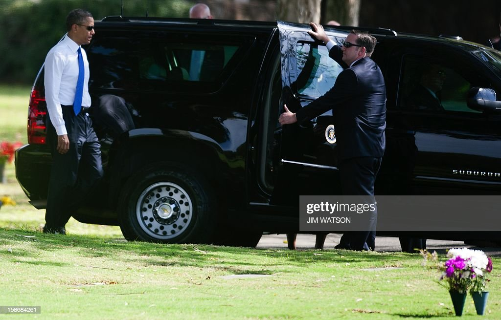 US President Barack Obama (L) returns to his SUV after visiting the grave site of Stanley Armour Dunham (March 23, 1918 – February 8, 1992), his maternal grandfather, at the National Memorial Cemetery of the Pacific in Honolulu, Hawaii, December 23, 2012. AFP Photo/Jim WATSON