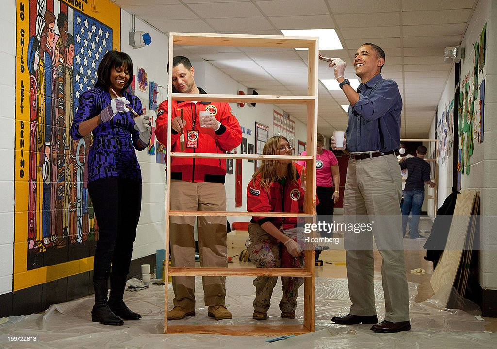 U.S. President Barack Obama, right, and first lady Michelle Obama, left, help to stain a bookshelf at Burrville Elementary School in Washington, D.C., U.S., on Saturday, Jan. 19, 2013. Joining the Obamas are Jeff Franco, center, executive director of City Year program, and Sheri Fisher, a City Year employee. The event was part of the National Day of Service, the first official event of the 57th presidential inauguration weekend. Photographer: Martin H. Simon/Pool via Bloomberg