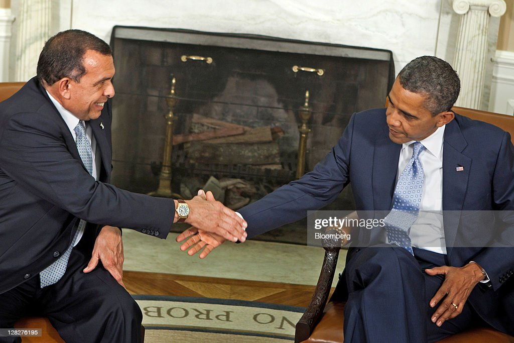 US President Barack Obama right and Porfirio Lobo president of Honduras left shake hands before a bilateral meeting in the Oval Office of the White...