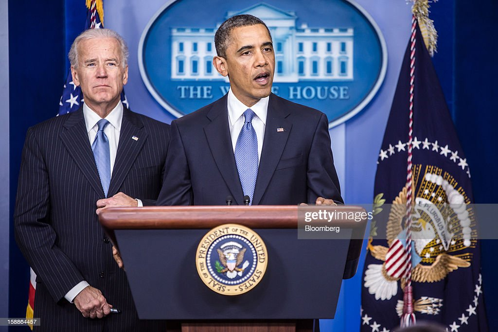 U.S. President Barack Obama, right, speaks as U.S. Vice President Joseph 'Joe' Biden looks on in the Brady Press Briefing Room at the White House in Washington, D.C., U.S., on Tuesday, Jan. 1, 2013. The House of Representatives passed legislation averting income tax increases for most U.S. workers after Republicans abandoned their effort to attach spending cuts that would have been rejected by the Senate. Photographer: Brendan Hoffman/Pool via Bloomberg