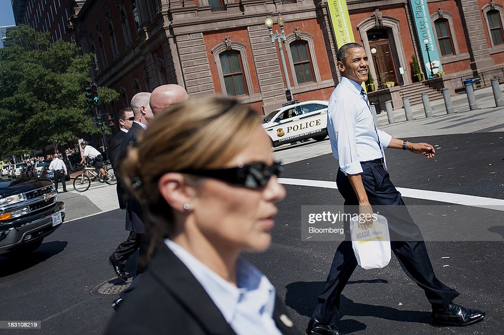 U.S. President Barack Obama, right, walks back to the White House after picking up lunch at a Taylor Gourmet Deli location on Pennsylvania Avenue in Washington, D.C., U.S., on Friday, Oct. 4, 2013. Obama canceled plans to attend two economic summits in Asia next week, a setback for his top foreign policy goal, as he remains in Washington to seek an end to the partial government shutdown. Photographer: Pete Marovich/Bloomberg via Getty Images