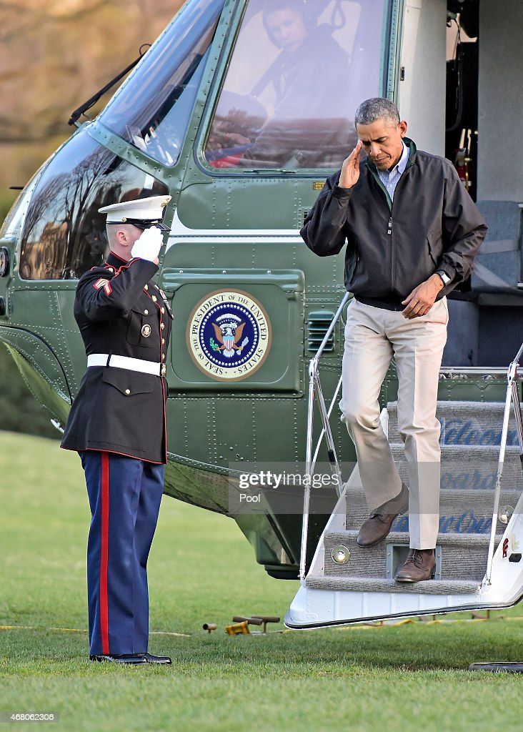 U.S. President Barack Obama salutes as he returns to the White House March 29, 2015 in Washington, DC. The president was returning from a two-day trip to Palm City, Florida where he played golf. Photo by Ron Sachs-Pool via Getty Images)