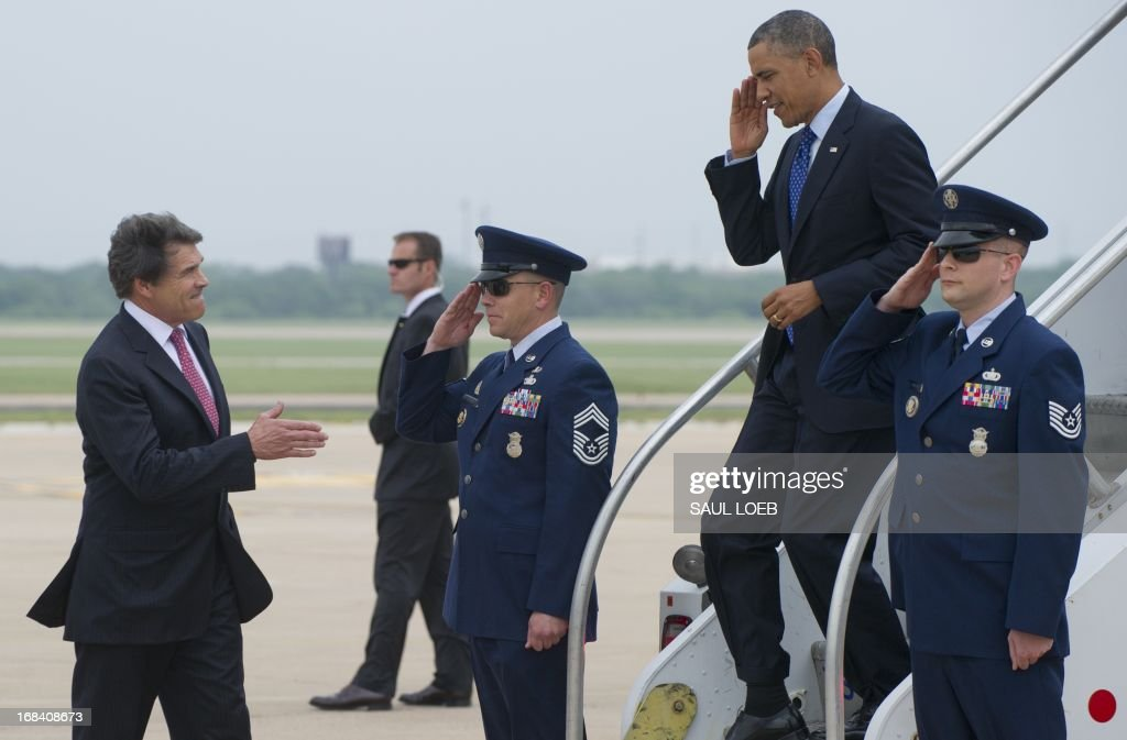 US President Barack Obama salutes as Texas Governor Rick Perry (L) reaches out to shake hands after arriving on Air Force One at Austin-Bergstrom International Airport in Austin, Texas, May 9, 2013. Obama will speak on the economy and job creation. AFP PHOTO / Saul LOEB