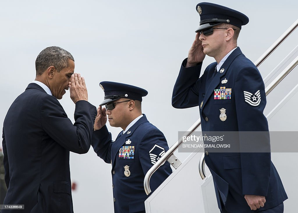 US President Barack Obama salutes military personnel as he boards Air Force One at Andrews Air Force Base July 24, 2013 in Maryland. Obama is traveling to Illinois and Missouri to speak about the economy. AFP PHOTO/Brendan SMIALOWSKI