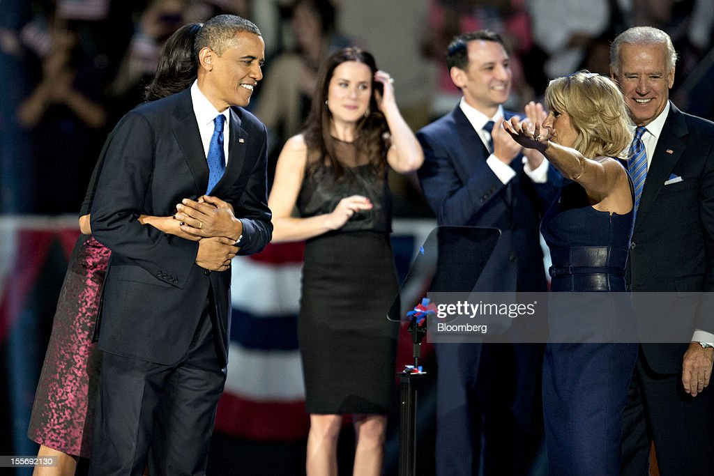 U.S. President Barack Obama, second left, is embraced by First Lady Michelle Obama as they speak to Jill Biden, second right, wife of U.S. Vice President Joseph 'Joe' Biden, right, during an election night rally in Chicago, Illinois, U.S., in the early morning on Wednesday, Nov. 7, 2012. Obama, the post-partisan candidate of hope who became the first black U.S. president, won re-election today by overcoming four years of economic discontent with a mix of political populism and electoral math. Photographer: Daniel Acker/Bloomberg via Getty Images