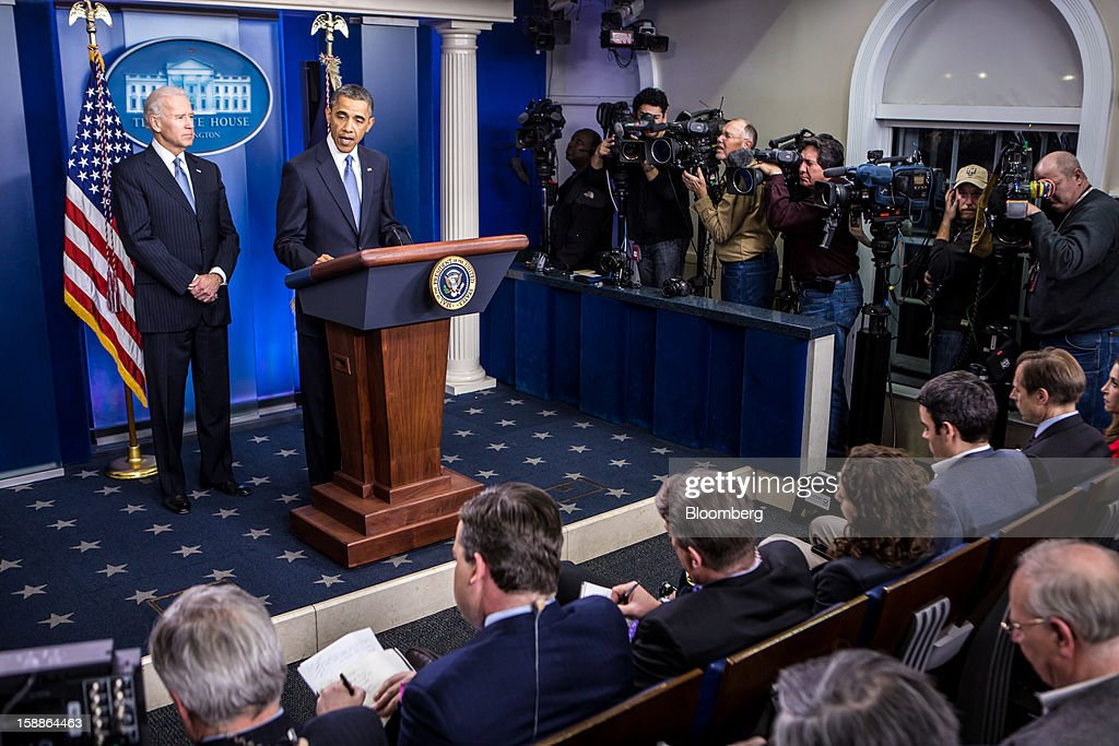 U.S. President Barack Obama, second left, speaks as U.S. Vice President Joseph 'Joe' Biden, left, looks on in the Brady Press Briefing Room at the White House in Washington, D.C., U.S., on Tuesday, Jan. 1, 2013. The House of Representatives passed legislation averting income tax increases for most U.S. workers after Republicans abandoned their effort to attach spending cuts that would have been rejected by the Senate. Photographer: Brendan Hoffman/Pool via Bloomberg