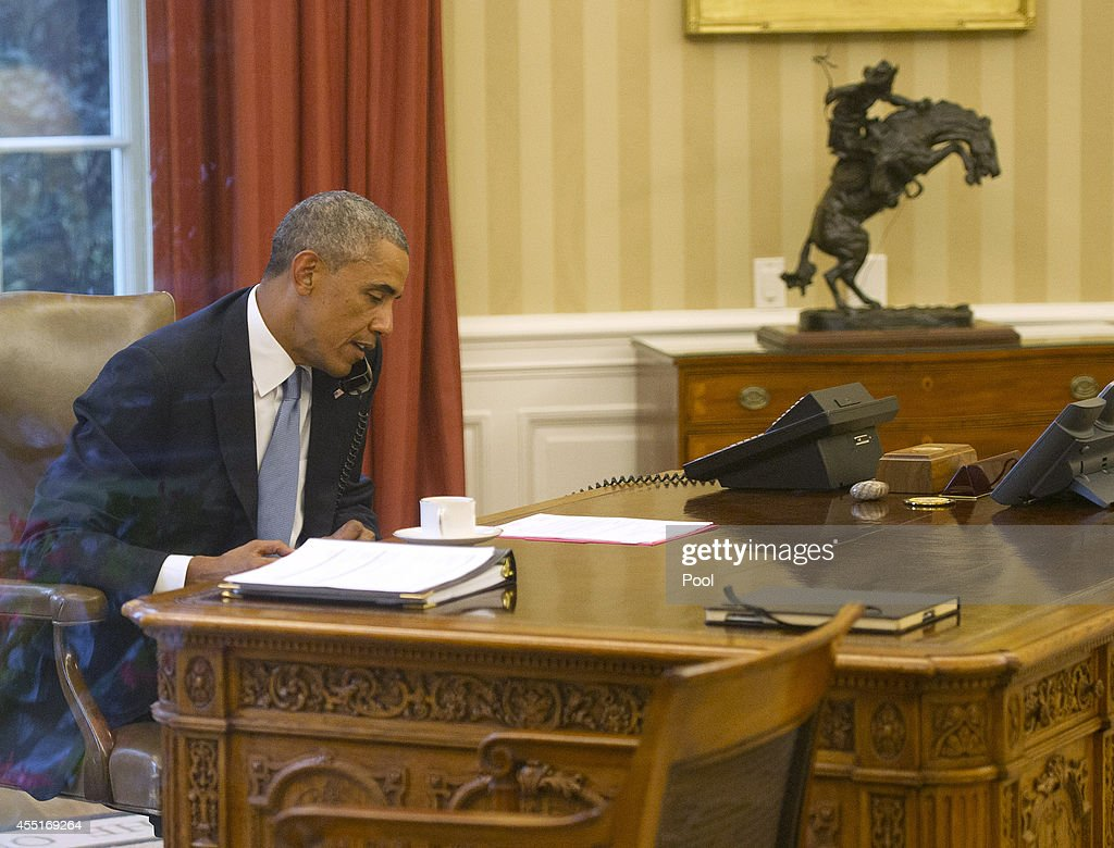 obama oval office. us president barack obama seen through an oval office window speaks on the phone