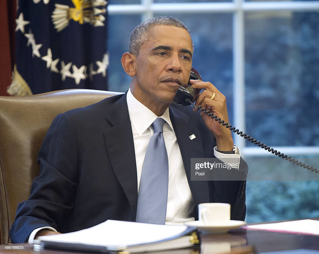 US President Barack Obama seen through an Oval Office window speaks on the phone with King Abdallah Abd al Aziz of the Kingdom of Saudi Arabia at the...