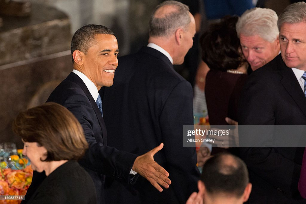 U.S. President <a gi-track='captionPersonalityLinkClicked' href=/galleries/search?phrase=Barack+Obama&family=editorial&specificpeople=203260 ng-click='$event.stopPropagation()'>Barack Obama</a> shakes hands as he and first lady Michelle Obama arrive at the Inaugural Luncheon in Statuary Hall on Inauguration day at the U.S. Capitol building January 21, 2013 in Washington D.C. President Obama was ceremonially sworn in for his second term today.