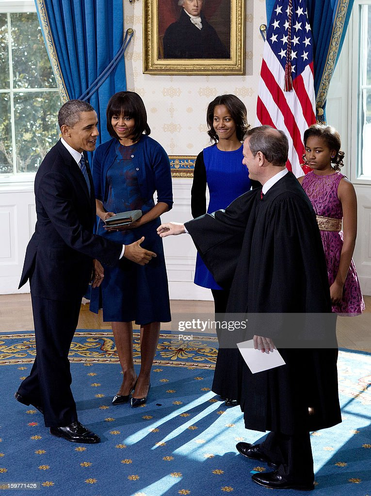 President Barack Obama (L) shakes hands U.S. Supreme Court Chief Justice John Roberts (2nd R) after takes the oath of office as first lady Michelle Obama (2nd L), daughter Malia (C) and Sasha (R) looks on in the Blue Room of the White House January 20, 2013 in Washington, DC. Obama and U.S. Vice President Joe Biden were officially sworn in a day before the ceremonial inaugural swearing-in.