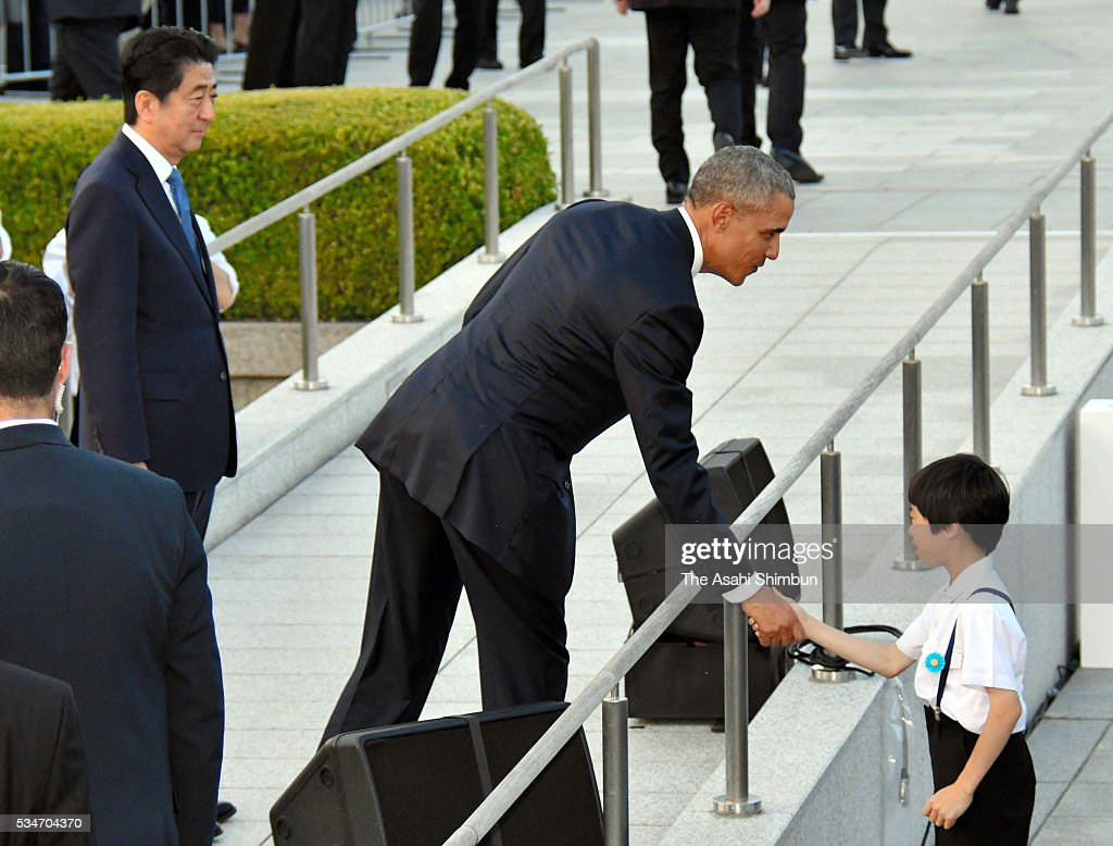 U.S. President <a gi-track='captionPersonalityLinkClicked' href=/galleries/search?phrase=Barack+Obama&family=editorial&specificpeople=203260 ng-click='$event.stopPropagation()'>Barack Obama</a> shakes hands with a boy while Japanese Prime Minister <a gi-track='captionPersonalityLinkClicked' href=/galleries/search?phrase=Shinzo+Abe&family=editorial&specificpeople=559017 ng-click='$event.stopPropagation()'>Shinzo Abe</a> watches at the Hiroshima Peace Memorial Park on May 27, 2016 in Hiroshima, Japan. Obama becomes the first sitting U.S. president to visit Hiroshima, where the first atomic bomb was dropped in 1945 at the end of World War II.
