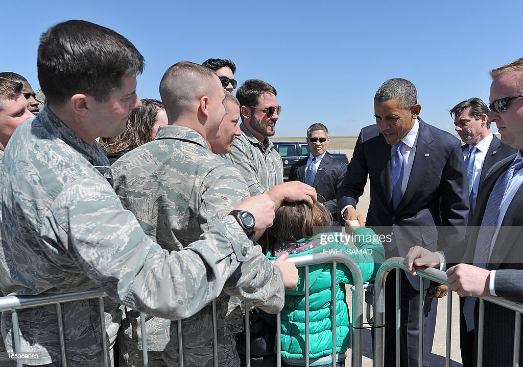 US President Barack Obama shakes hands with a child upon arriving at the Buckley Air Force Base in Denver, Colorado, on April 3, 2013., Obama has demanded votes on measures including a requirement for background checks on all gun purchases, limits on high capacity ammunition magazines, a reinstated assault weapons ban, new gun trafficking laws, and new school safety plans. But the assault weapons ban push appears certain to fail to get sufficient support in the Senate, following a huge campaign by the gun lobby and opposition from Republicans and Democrats from conservative and rural areas. AFP PHOTO/Jewel Samad