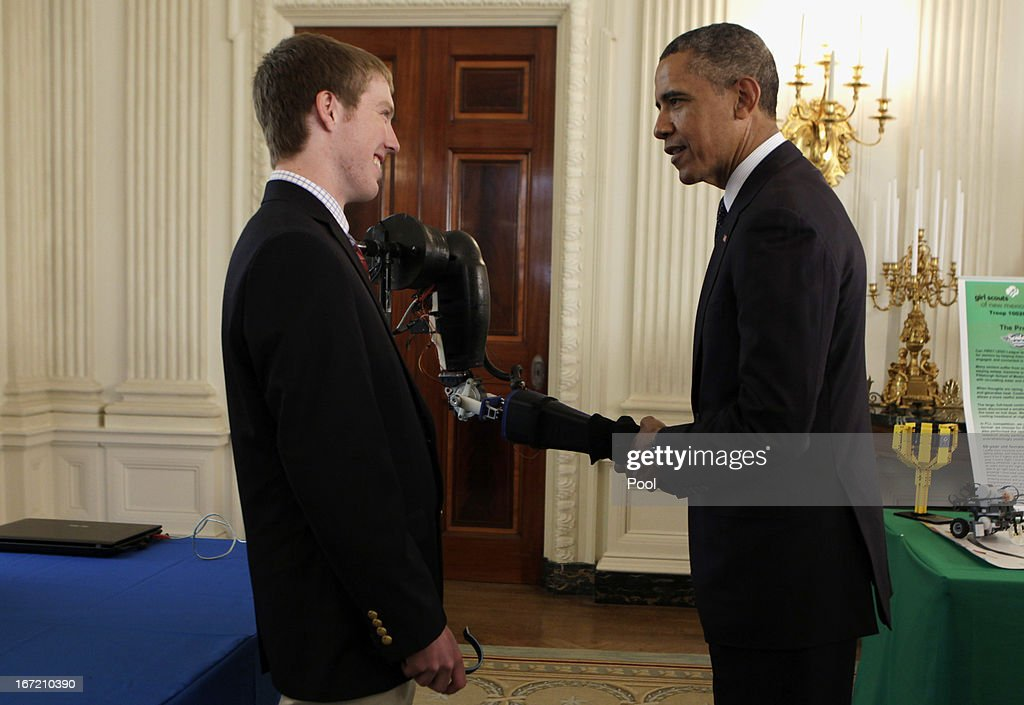 U.S. President Barack Obama shakes hands with a robotic arm, created and presented by second place winner at International Science and Engineering Fari, Easton LaChappelle, from Mancos Colorado in the State Dining Room of the White House during the White House Science Fair April 22, 2013 in Washington, DC. The White House Science Fair celebrates the student winners of a broad range of science, technology, engineering and math (STEM) competitions from across the country. The first White House Science Fair was held in late 2010.