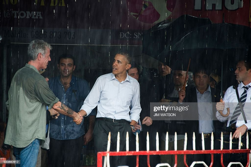 US President Barack Obama (C) shakes hands with Anthony Boudain (L), a chef and food critic who fronts a travel show about hidden culinary gems around the world, after visiting a local shopping district in Hanoi on May 24, 2016. Obama, currently on a visit to Vietnam, earlier met with civil society leaders including some of the country's long-harassed critics on May 24. / AFP / JIM