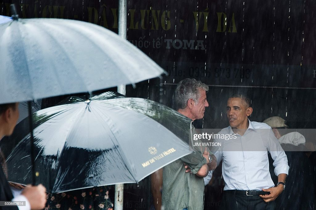 US President Barack Obama (R) shakes hands with Anthony Boudain (C), a chef and food critic who fronts a travel show about hidden culinary gems around the world, after visiting a local shopping district in Hanoi on May 24, 2016. Obama, currently on a visit to Vietnam, earlier met with civil society leaders including some of the country's long-harassed critics on May 24. / AFP / JIM
