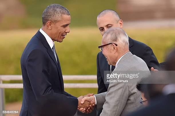 S President Barack Obama shakes hands with atomic bomb survivor Shigeaki Mori during his visit to the Hiroshima Peace Memorial Park on May 27 2016 in...