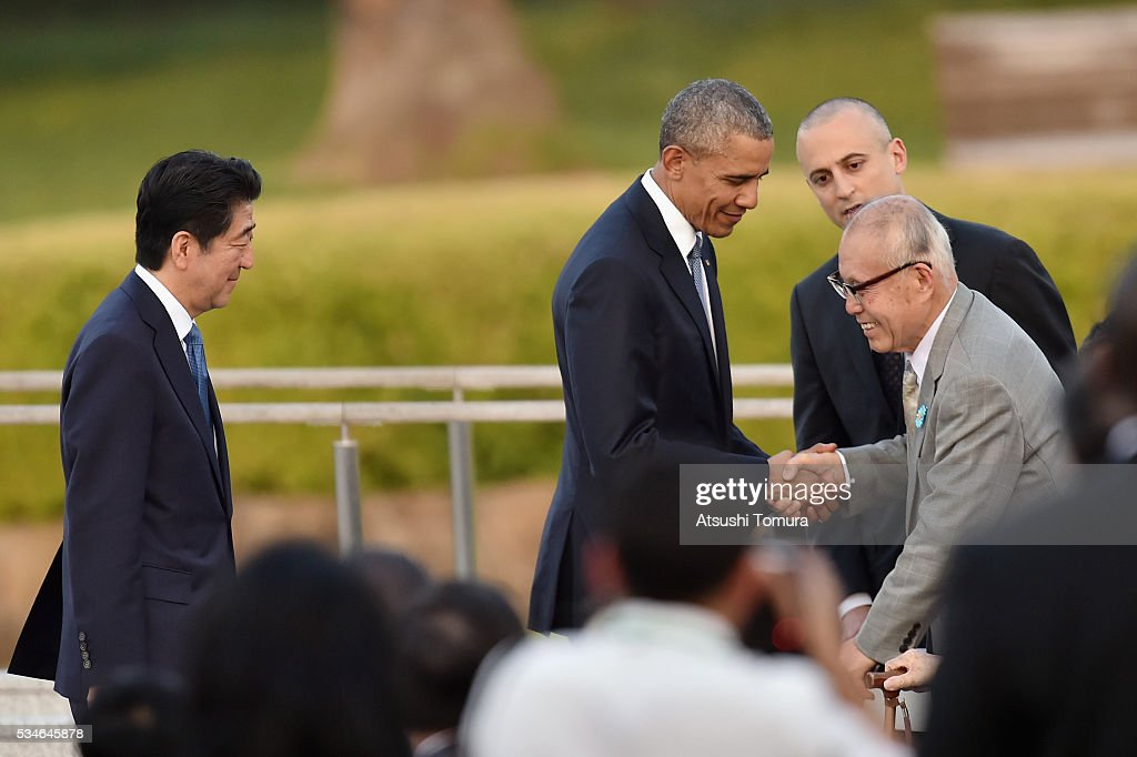 U.S. President Barack Obama (C) shakes hands with atomic bomb survivor Shigeaki Mori (R) as Japanese Prime Minister Shinzo Abe (R) looks on during the visit to the Hiroshima Peace Memorial Park on May 27, 2016 in Hiroshima, Japan. It is the first time U.S. President makes an official visit to Hiroshima, the site where the atomic bomb was dropped in the end of World War II on August 6, 1945.