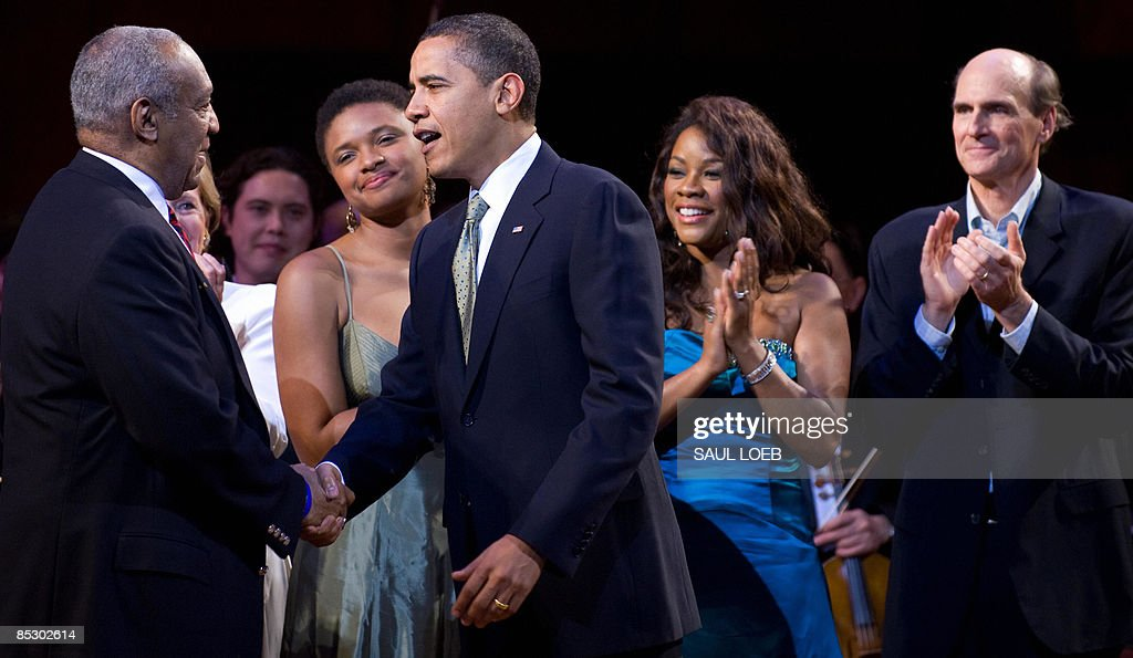 US President <a gi-track='captionPersonalityLinkClicked' href=/galleries/search?phrase=Barack+Obama&family=editorial&specificpeople=203260 ng-click='$event.stopPropagation()'>Barack Obama</a> shakes hands with <a gi-track='captionPersonalityLinkClicked' href=/galleries/search?phrase=Bill+Cosby&family=editorial&specificpeople=206281 ng-click='$event.stopPropagation()'>Bill Cosby</a> (L) before singing Happy Birthday to Massachusetts Senator Ted Kennedy during a musical birthday salute to Kennedy at the Kennedy Center in Washington, DC, March 8, 2009. Standing alongside Obama are: Lizz Wright (2nd L), Denyce Graves (2nd R) and James Taylor (R). AFP PHOTO / Saul LOEB
