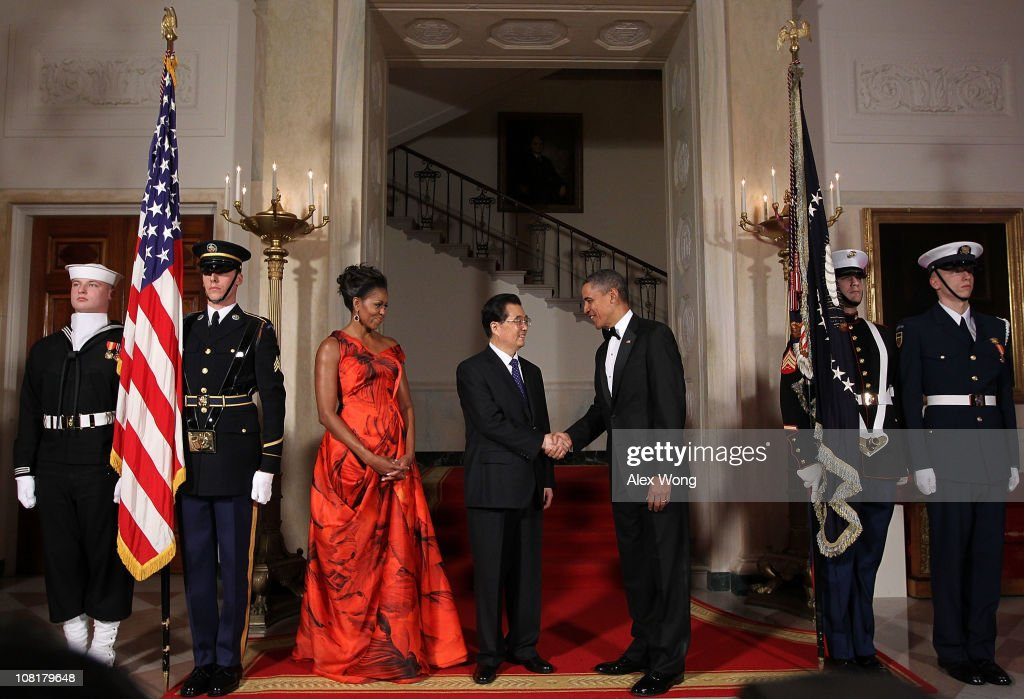 U.S. President Barack Obama (R) shakes hands with Chinese President Hu Jintao (C) as first lady Michelle Obama looks on as they pose for the official photo at the Grand Staircase of the White House January 19, 2011 in Washington, DC. Obama is hosting a state dinner for Hu this evening.