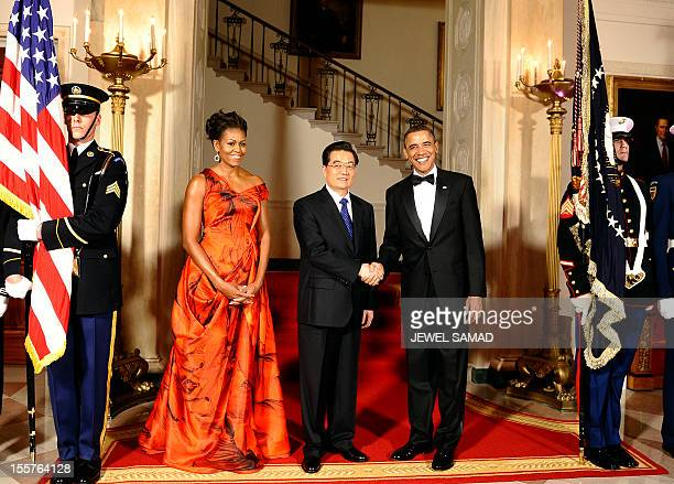 US President Barack Obama shakes hands with Chinese President Hu Jintao as First Lady Michelle Obama looks on on the Grand Staircase at the White...